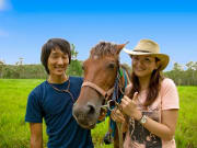 couple posing with horse lush green background