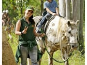kid riding a white horse with guide holding reins