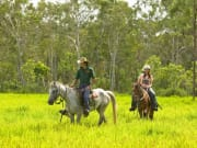 guide leads two travelers in horseback ride