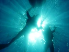 Light shining on swimmers in the Blue Cave