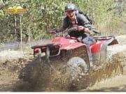man riding an ATV quad bike on muddy water
