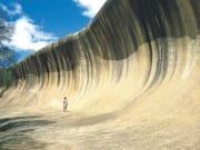 woman standing in front of wave rock australia