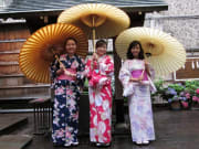 3 women wearing yukata, holding Japanese umbrellas