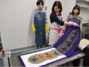 Pulling a stencil layer off to show chusen dyeing
