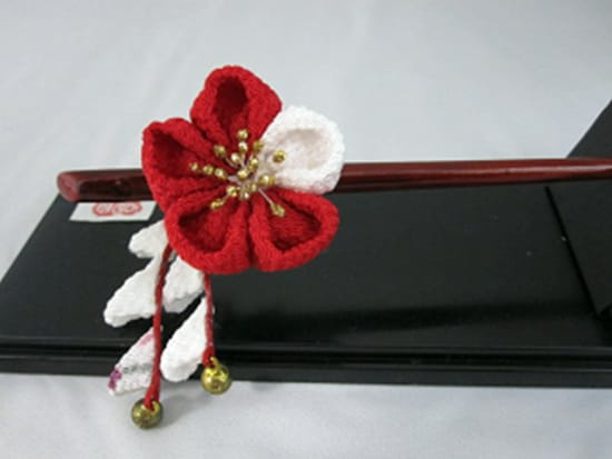 A red and white flower hair stick