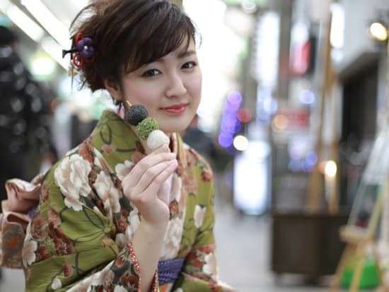 Japanese girl in kimono posing with dango