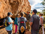 guide explaining about uluru to tourists