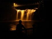 Paronella park at night man looking at the falls