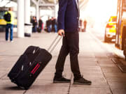 man carrying luggage to board shuttle service