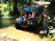 two women sitting at the hood of military hummer