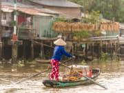 Mekong delta woman selling bread aboard a boat
