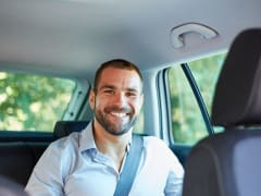 man with wide smile aboard a privat car