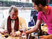 Elderly woman being served wine