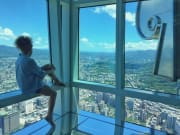tourist at Taipei 101 observatory looking at view