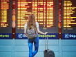 airport woman looking at flight schedule