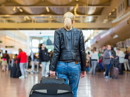 woman carrying black luggage inside the airport