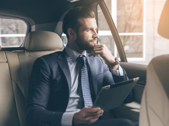 businessman thinking inside the car holding ipad