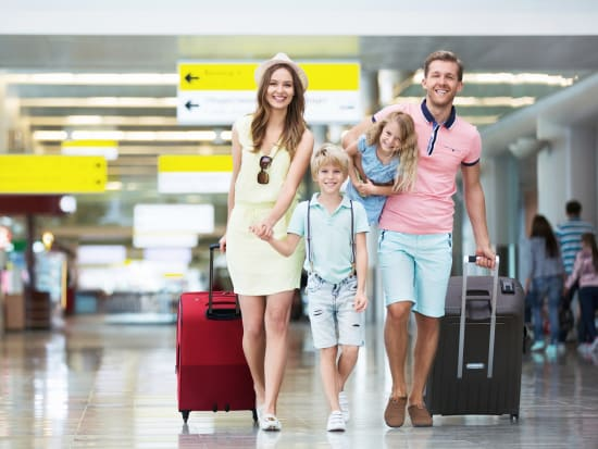 young family mom dad and kids at the airport