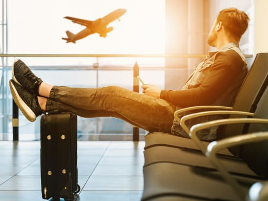 man sitting with foot atop his suitcase airplane