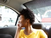 black woman on the phone inside private vehicle