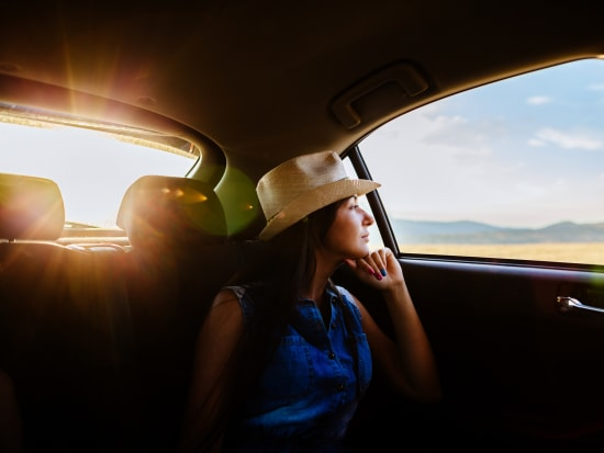 woman sitting inside car looking at outside view
