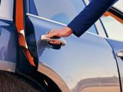 driver opening car door for passenger, back seat