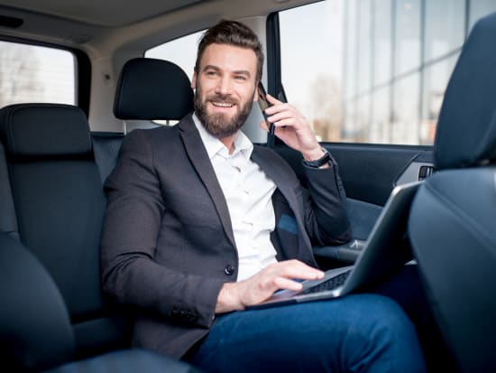 man talking on the phone inside a private car