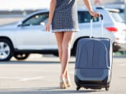 woman in heels and black dress carrying luggage