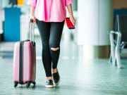 woman in pink carrying pink luggage in airport