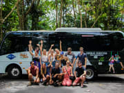 group photo with gray line bus at the back