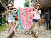 shifen old railway tracks women taking photos