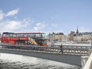 city sightseeing bus passing by bridge over water