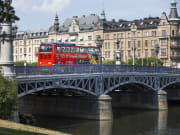 red city sightseeing bus crossing a bridge