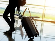 traveler with luggage at airport sunset background