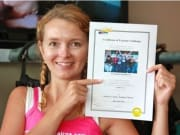 woman holding certificate of skydive completion
