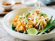 plate of pad thai with lime bean sprouts chicken