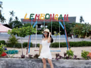woman posing in front of colorful Lembongan sign
