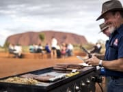 tour guide grilling sausages in uluru, sunset bbq
