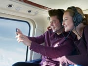 couple on helicopter tour taking photos of view
