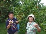 農園のコーヒー豆の木の前にて